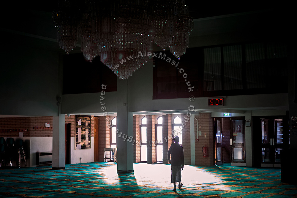 A young member of the Islamic community is walking around Birmingham Central Mosque.