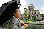 TAEKO TERAMAE Hiroshima A-bomb survivor, sitting at a riverbank inside the Peace Memorial Park, in front of the remains of the A-bomb Dome. On the 6th of August 1945 she was in her third year of  Shintoku girls' high school and was engaged in a in the telephone exchange service as a mobilized student at the Hiroshima Central Telephone Office. She was at work when the bomb fell and she was badly injured by pieces of broken glass that cut her face, resulting in loosing eyesight on her right eye. She survived by swimming to cross a river to a safer area, with the help of one of her teachers who later died. She is one of the survivors who tell their stories in the Hiroshima Peace Memorial Museum.