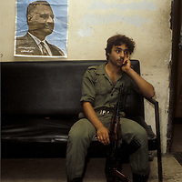 A soldier loyal to Gamal Abdel Nasser sits at his guard post in Beirut, Lebanon under a worn poster of Nasser in the wake of the assassinaiton of Anwar Sadat in 1981.