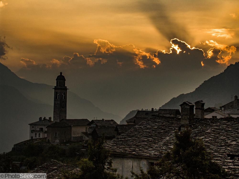 Sunset pierces orange thunderhead clouds at Soglio village, Bregaglia Valley, Graubünden (Grisons) canton, Switzerland, the Alps, Europe.