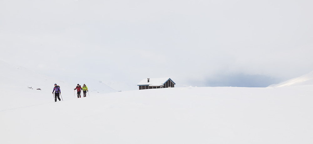 Kiya Riverman (l-r), Anouk Vlug, and Nate Stevens ski from a backcountry cabin at the mouth of Foxdalen in Adventdalen, Svalbard.