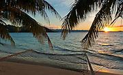 Hammock and palm trees on beach at sunset, Matangi Private Island Resort, Fiji.