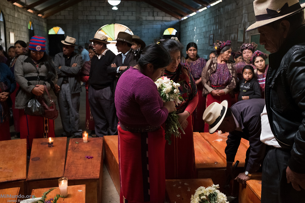 Friends and family gather as the human remains of 36 Ixil Mayan war victims are waked by surviving family members before a proper burial. Most of the victims, exhumed from mass graves in Xe'xuxcap, near Acul, starved in the mountainside while fleeing State-led repression in 1982. Most of the remains, exhumed by members of the Forensic Anthropology Foundation of Guatemala (FAFG) in 2013, were identified using DNA analysis and buried 35 years after their death. Acul, Nebaj, Quiché, Guatemala. February 3, 2017.