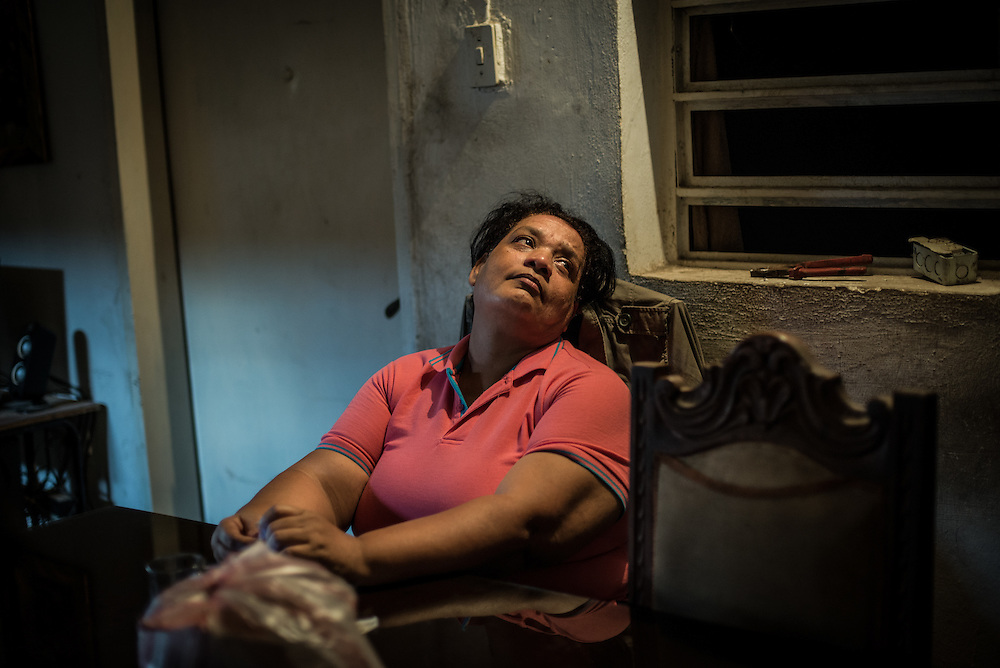 """MARACAY, VENEZUELA - JULY 15, 2016: Evelin RodrÍguez sighs in frustration while explaining how difficult her life is caring for her two schizophrenic sons, Gerardo and Accel, in a country suffering from severe shortages of medicines, including the psychiatric drugs that she needs to keep her sons' conditions stabilized. It is an exhausting task taking care of them and going from pharmacy to pharmacy for hours searching for the medicines that her sons need, that she is rarely able to find. She copes by reducing their doses, and by sharing their prescriptions depending on which son needs the medicine the most each day. Evelin is a lawyer, but has quit all of her work since Accel attempted to cut off his arm after three weeks without his medicine. Evelin now spends her days looking after Accel and Gerardo, too afraid to leave them alone because they might hurt themselves.  """"I am tired,"""" she said. """"This is too much sometimes"""". PHOTO: Meridith Kohut for The New York Times"""