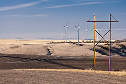 Electric power transmission lines cross wheat fields near electric generating windmills in the Palouse region of eastern Washington, USA