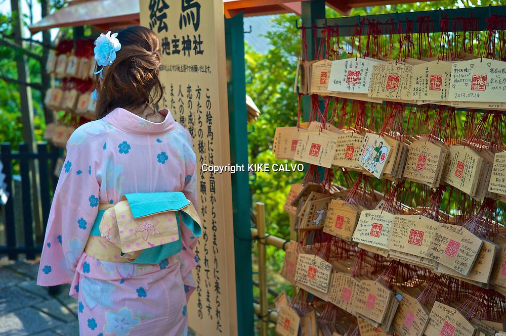 Japanese woman wearing traditional kimono next to Buddhist wooden prayers at the Kiyomizu Temple.