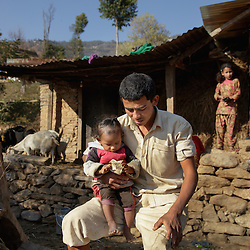 Holding his youngest child, Durga, now 26, sits in frustration in front of the rebuilt shed he shares with Niruta, now 24, their three children, a water buffalo, and a handful of chickens and goats. <br />