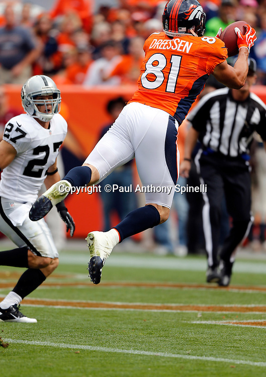 Denver Broncos tight end Joel Dreessen (81) leaps and catches a first quarter touchdown pass good for a 7-0 lead while covered by Oakland Raiders free safety Matt Giordano (27) during the NFL week 4 football game on Sunday, Sept. 30, 2012 in Denver. The Broncos won the game 37-6. ©Paul Anthony Spinelli