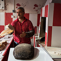 A baker in Van stretches dough for lavash by passing it from palm to palm. The dough will be stretched over the pillow then slapped to the side of a tandir oven (just behind him).