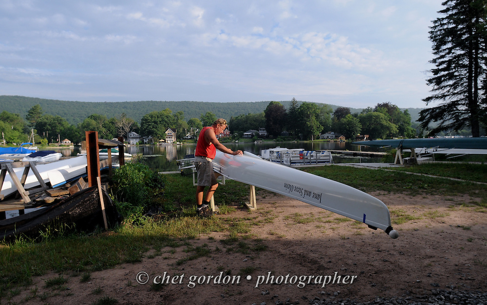 A man pauses near a four-man boat after a morning row in Greenwood Lake, NY on Tuesday, July 9, 2013.  © Chet Gordon/THE IMAGE WORKS