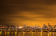 On a cold February evening, the Chicago skyline glows under a low cover of clouds. Seen here from Belmont Harbor, lights reflect off of a frozen Lake Michigan.