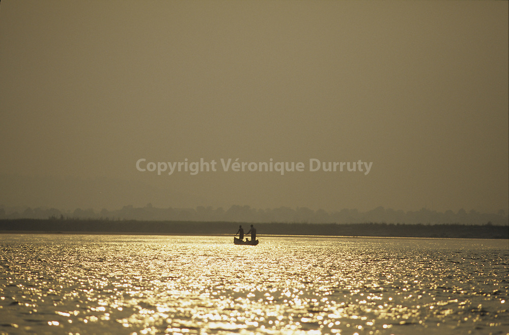 SUNSET. DUGOUT ON THE CONGO RIVER BETWEEN BOTH CONGO
