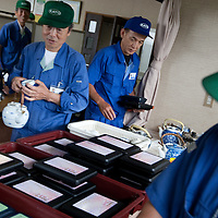Elderly workers take their bento-box lunch, which the company provides at a cost to each worker of JPN Yen 300, at Kato (a light industry company) in Nakatsugawa, Japan, Monday 21st June 2010. Kato company has a workforce of 100 people, 50% of whom are 60 years of age or older. The elderly work force earn JPN ¥800-1,000 per hour, but receive no annual bonus or pay rise.