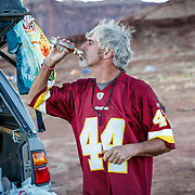 SHOT 10/16/16 6:12:12 PM - Paul Hobson of Steamboat Springs, Co. takes a swig of rum while camping at the Airport camp spot on the White Rim. The White Rim is a  mountain biking trip in Canyonlands National Park just outside of Moab, Utah. The White Rim Road is a 71.2-mile-long unpaved four-wheel drive road that traverses the top of the White Rim Sandstone formation below the Island in the Sky mesa of Canyonlands National Park in southern Utah in the United States. The road was constructed in the 1950s by the Atomic Energy Commission to provide access for individual prospectors intent on mining uranium deposits for use in nuclear weapons production during the Cold War. Four-wheel drive vehicles and mountain bikes are the most common modes of transport though horseback riding and hiking are also permitted.<br /> (Photo by Marc Piscotty / &copy; 2016)