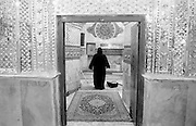 A woman in black chador cleaning the women's side of the Mausoleum of the son of the 3rd Imam in the center of Bazaar. Tehran, Iran, 2007