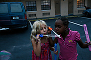 MELISSA LYTTLE   |   Times<br /> SP_345156_LYTT_MOTEL_5 (November 22, 2011, St. Petersburg, FL) Valerie Drinkwater, 6, blows bubbles with Deansya Manning, 6, in the parking lot of the Mosley Motel, which has been recently gated and secured, with guests having to sign in at the front office with a picture ID, and cars needing a gate code. Since only a handful of the residents at the Mosley have vehicles, the parking lot ends up becoming a big playground for the kids there, usually housing nightly football games, foot races, chalk drawings and on this night in October, bubbles that were handed out by a local church group.  [MELISSA LYTTLE, Times]