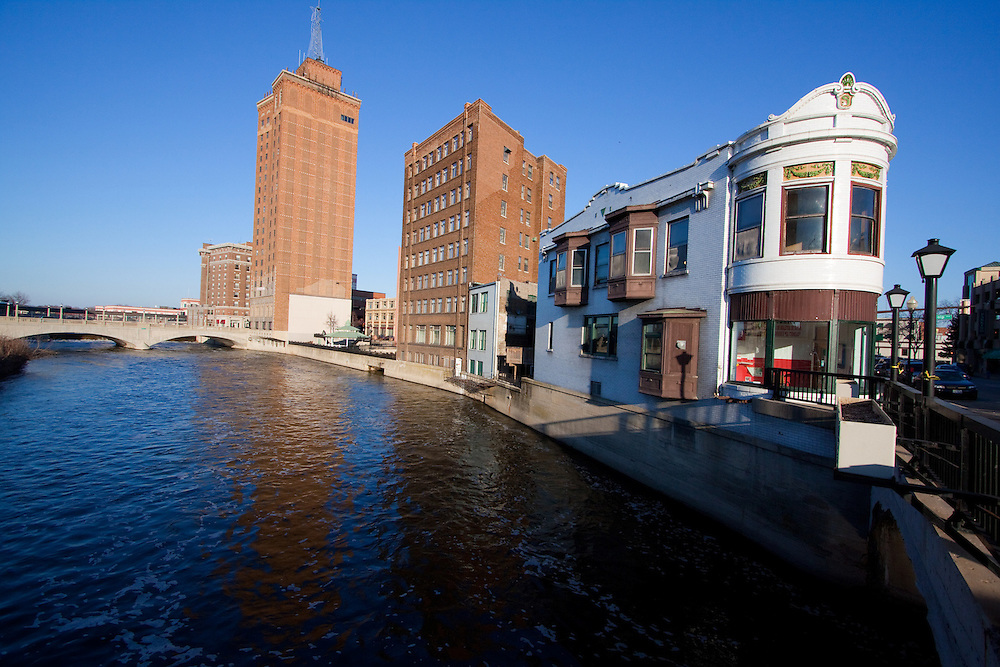 The Fox River flows through the downtown area of Aurora, IL, splitting part of it in two. In the distance is the Leland Tower, and the historic Sherer Building, with it's rounded end overlooking the river, is in the foreground.