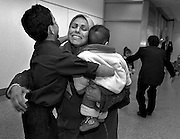 Saleh rushes to embrace his mother, Hadia, and new baby brother, Ali, at San Francisco International Airport.  At right, Raheem swoops up Mawra and Zahra, the daughters he hasn't seen in over a year.