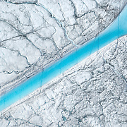 Meltwater flows across the top of the Greenland ice sheet which has been sullied by cryoconite, 65 km southeast of Ilulissat, August, 2014. The presence of cryoconite, or ash and soot deposited on top of the ice sheet, triples the melt rate atop the ice sheet.
