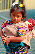 GUATEMALA, HIGHLANDS, MARKETS Chichicastenango; famous Sunday market, with young Maya indian girl and a live rooster  carried in her rebozo
