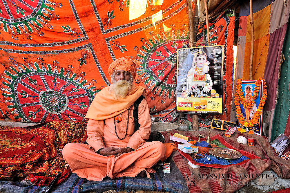 A Sadhu (or Naga Baba) in a tent  in Kumbh Mela. Sadhu is an ascetic holy man who devotes himself to the goal of moksha or liberation so that soul can overcome the cycle of reincarnation. The Sadhu tradition in India has a long history which can be traced back to the Vedic Age. Such a Hindu ascetic or a monk renounces worldly pleasures in pursuit of higher values of life in order to attain enlightenment. Through strict and hard practice Sadhu detached themselves from  pleasures and pains of human life which makes them indifferent from world and transports them to the metaphysical world..Etymologically Sadhu is a Sanskrit word which means a wise man who renounces the world and all worldly pleasures in quest of spirituality, which ultimately lead them to enlightenment. In order to achieve the zenith of human life they live in caves, temples, forests and hill top, practicing strict code and conduct.