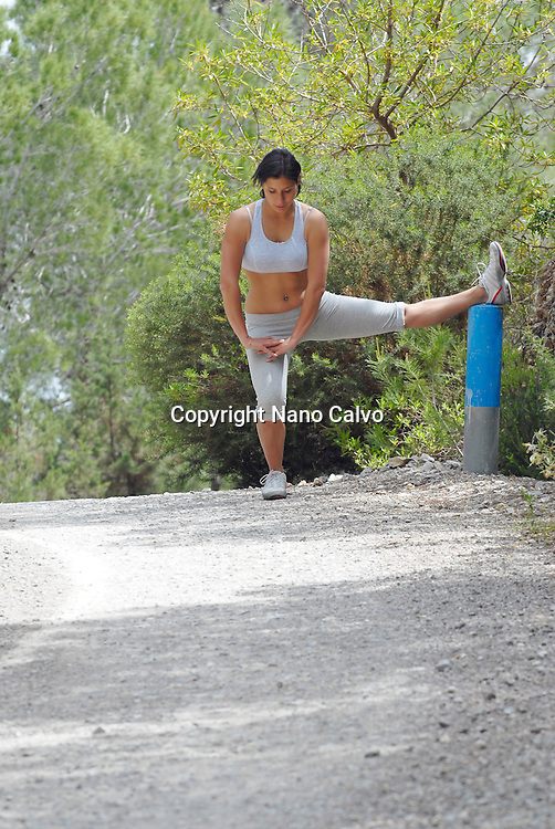 Young brunette woman stretches in nature