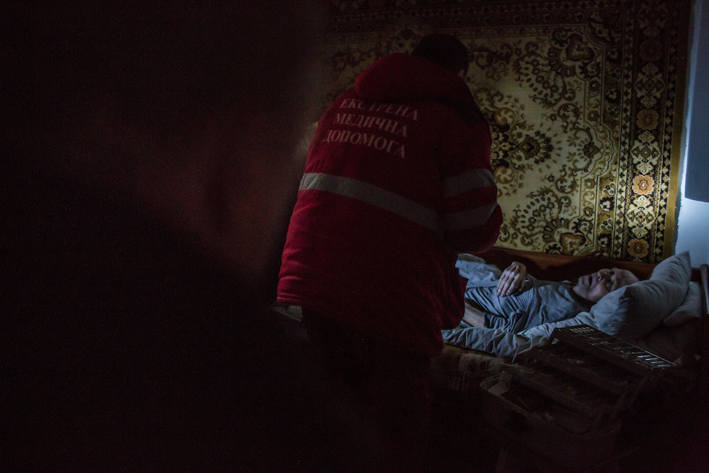 DONETSK, UKRAINE - JANUARY 28, 2015: A 100-year-old man is tended to by a paramedic in the Petrovskyi district of Donetsk, Ukraine. The area, in the city's southwest, is close to heavy front-line fighting in Marinka. CREDIT: Brendan Hoffman for The New York Times