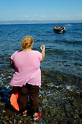 Local woman directing a refugee boat on where to arrive.<br /> Refugees arriving on beaches near Molyvos village in Lesvos island. Thousands of them come from Turkey, crossing the sea border on inflatable dinghy boats, on a dangerous trip that has claimed many lives. Local people or NGOs expect them and help them in some places but after their arrival, most of them have to walk to the nearest village where they can hope for a places on busses that can take them to the city of Mytilene where they can register and eventually board on a ferry to Athens. Many decide to walk the distance as the busses aren&rsquo;t enough to accommodate the large number of people that arrive daily.