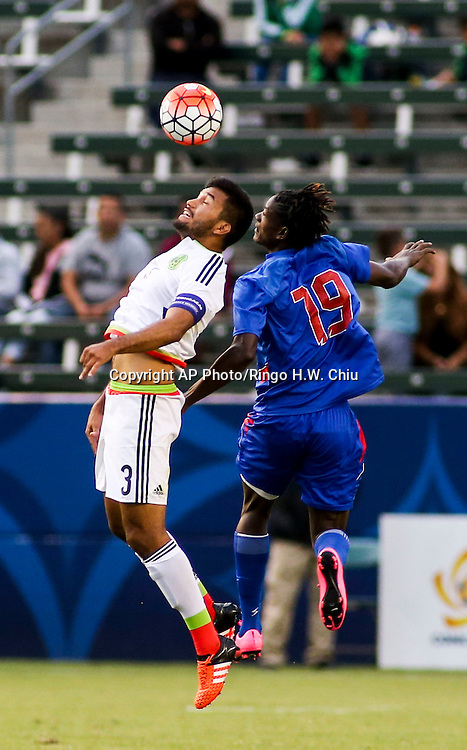 Mexico defender Hedgardo Marín Arroyo, left, and aiti forward Manchini Telfort fight for the head ball in the second half of a CONCACAF men's Olympic qualifying soccer match in Carson, Calif., Sunday, Oct. 4, 2015. Mexico won 1-0. (AP Photo/Ringo H.W. Chiu)