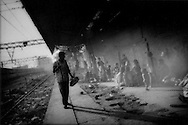 Lowest of the low: Commuter eyes untouchable (Dalit) squatters who have colonized abandoned train platform, Howrah Station, Calcutta, India.  This is home to a new generation of impoverished Dalit children.