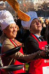 London, February 17th 2015. Members of Parliament put their dignity aside for a bit of fun as they compete in the annual Parliamentary Pancake Race in Victoria Tower Gardens adjacent to the House of Lords.  PICTURED: Sophie Ridge of Sky News and Ben Wright of the BBC practice tossing their pancakes prior to the start of the race.