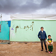 Cousins, Noor, 9, and Khalid, 3, outside of Noor's family caravan.  This winter has been brutal for Syrian refugees across the Middle East. Families who have now endured years away from their war-torn home still do not have the safe shelter or warm clothes needed to withstand freezing weather. Zaatari Camp for Syrian Refugees, Jordan, February 2015.