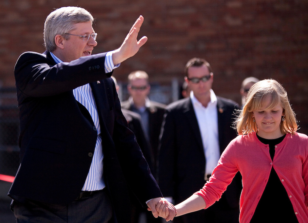 Conservative leader Prime Minister Stephen Harper waves to supporters  as he and his daughter Rachel leave a polling station at St. Augustine Catholic school in Calgary, Alberta after casting his ballot in the federal election.<br /> AFP/GEOFF ROBINS/STR