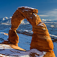 Delicate Arch against the La Sal Mountains near Moab, Utah with a blanket of snow across the ground.