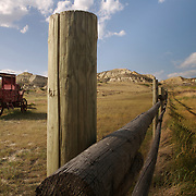 """An old abandoned stagecoach shares the landscape with a wooden fence that stretches towards North Dakota's Badlands near Medora.  ..The stark prairie landscape, with it's towering buttes, jaw-dropping chasms and surreal spires, is the gateway to the """"Old West""""...Nearby Theodore Roosevelt National Park draws thousands of visitors each year to North Dakota's western border.  photo by David Peterson.."""