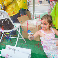 A girl makes use of markers and a clear tent wall in Copley Square at the Boston Book Festival.