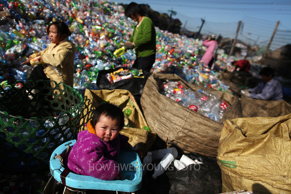 epa02997003 One-year-old migrant child Jiang Xingyu looks on as her family members sort out empty plastic bottles in a recycling centre in Changping district on the outskirts of Beijing, China, 09 November 2011. One of the largest in Beijing, the recycling centre is slated to be closed by the end of the year, leaving many of its mainly migrant community bewildered and uncertain of their livelihoods. This comes even as China is increasingly pressured to clean up its environment as two decades of rapid development resulted in massive land and air pollution.  EPA/HOW HWEE YOUNG