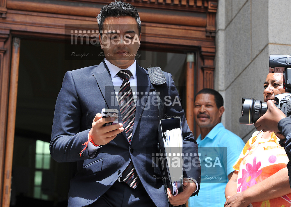 CAPE TOWN, SOUTH AFRICA - Monday 20 October 2014, Preyen Dewani, brother of Shrien Dewani, checks his cell phone as he leaves the court during Day 6 of the Shrien Dewani trial at the Western Cape High Court before Judge Jeanette Traverso. Dewani is caused of hiring hit men to murder his wife, Anni. Anni Ninna Dewani (n&eacute;e Hindocha; 12 March 1982 &ndash; 13 November 2010) was a Swedish woman who, while on her honeymoon in South Africa, was kidnapped and then murdered in Gugulethu township near Cape Town on 13 November 2010 (wikipedia).<br /> Photo by Roger Sedres