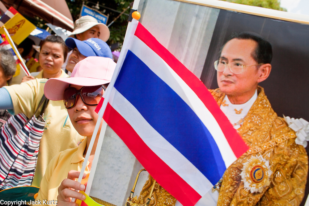 05 MAY 2010 - BANGKOK, THAILAND: A woman holds up a photo of Thai King Bhumibol Adulyade and the Thai flag while she waits for his motorcade, Wednesday May 5. Wednesday was Coronation Day in Thailand, marking the 60th anniversary of the coronation of Thai King Bhumibol Adulyade, also known as Rama IX. He is the world's longest serving current head of state and the longest reigning monarch in Thai history. He has reigned since June 9, 1946 and his coronation was on May 5, 1950, after he finished his studies. The King is revered by the Thai people. Thousands lined the streets around the Grand Palace hoping to catch a glimpse of the King as his motorcade pulled into the palace. The King has been hospitalized since September 2009, making only infrequent trips out of the hospital for official functions, like today's ceremonies.   PHOTO BY JACK KURTZ