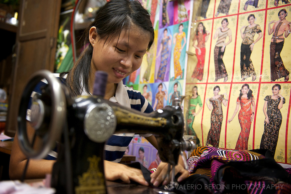 A dressmaker at the sewing machine next to a poster showing her collection of clothes in a market in Rangoon.
