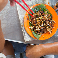 a Char kueh kok (radish cake) seller eats a plate of his own making. Chow Rasta Market, George Town, Penang, Malaysia