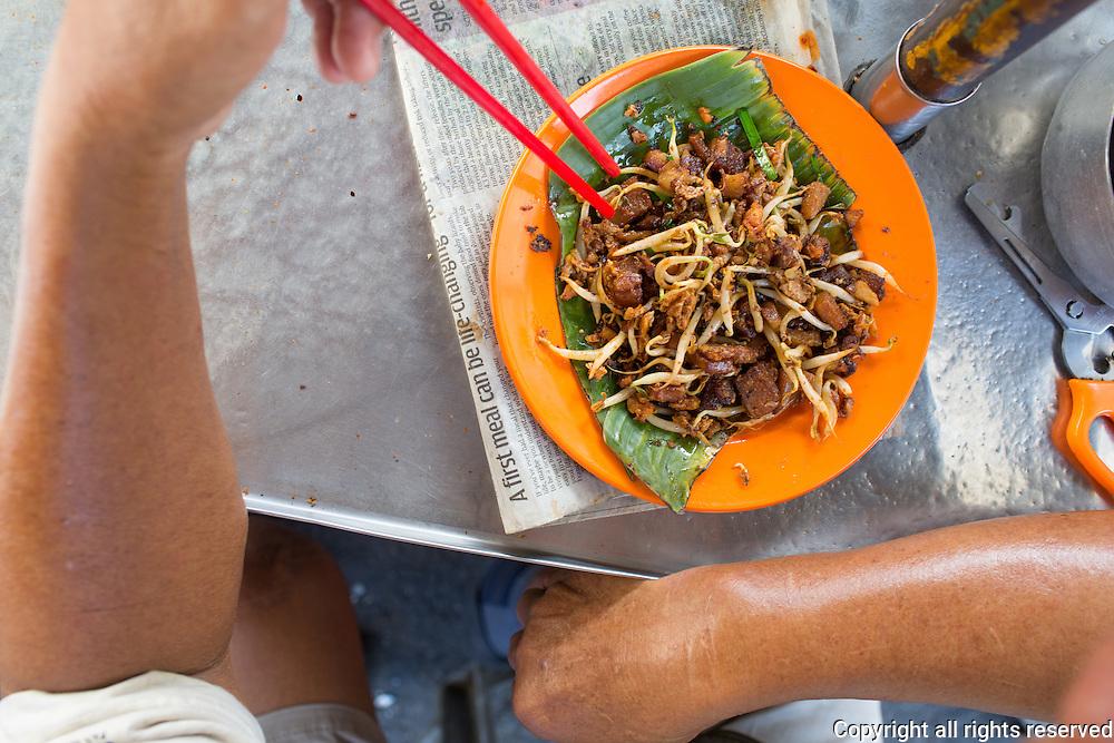 a Char kueh kok (radish cake) seller eats a plate of his own making. Chow Rasta Market, George Town, Penang, Malaysia