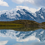 "Gspaltenhorn (3437 meters) reflects in Grauseeli lake on Schilthorn mountain near Birg cable car station in the Berner Oberland, Switzerland, the Alps, Europe. UNESCO lists ""Swiss Alps Jungfrau-Aletsch"" as a World Heritage Area (2001, 2007). Panorama stitched from 2 overlapping images."