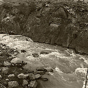 Suspension footbridge in Patagonia, Chile, South America panoramic sepia-toned black & white photograph.