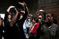 Pompei, Napoli. Turisti in visita agli scavi archeologici di Pompei si coprono gli occhi, abbagliati dalla  luce proveniente dall'alto del soffitto all'interno delle Terme Stabiane; A group of tourists inside the Baths Stabiane of archaeological site of Pompeii.