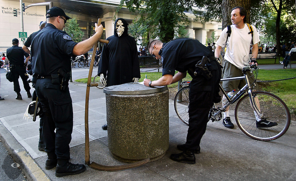 The Grim Reaper has his scythe confiscated by Portland Police as a safety concern. He was one of many protestors take to the streets about the Federal Courthouse to show their displeasure of the visit of U.S. Attorney John Ashcroft.