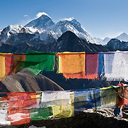 "Atop Gokyo Ri, admire Mount Everest, Himalayan peaks, and prayer flags. Mount Everest (center left; 29,029 feet / 8848 meters), the highest mountain on Earth, has the older name of Chomolungma or Qomolangma (""Goddess Mother of the Earth"" in Tibetan). To the right are Lhotse and Makalu (both higher than 8000 meters). In 1865, Andrew Waugh, the British surveyor-general of India named the mountain for his chief and predecessor, Colonel Sir George Everest. In the 1960s, the Government of Nepal named the mountain Sagarmatha, meaning ""Goddess of the Sky"". The mountain, which is part of the Himalaya range in High Asia, is located on the border between Nepal and Tibet, China. These colorful Tibetan Buddhist prayer flags invoke compassion. Sagarmatha National Park was created in 1976 and honored as a UNESCO World Heritage Site in 1979. Published in ""Light Travel: Photography on the Go"" book by Tom Dempsey 2009, 2010."