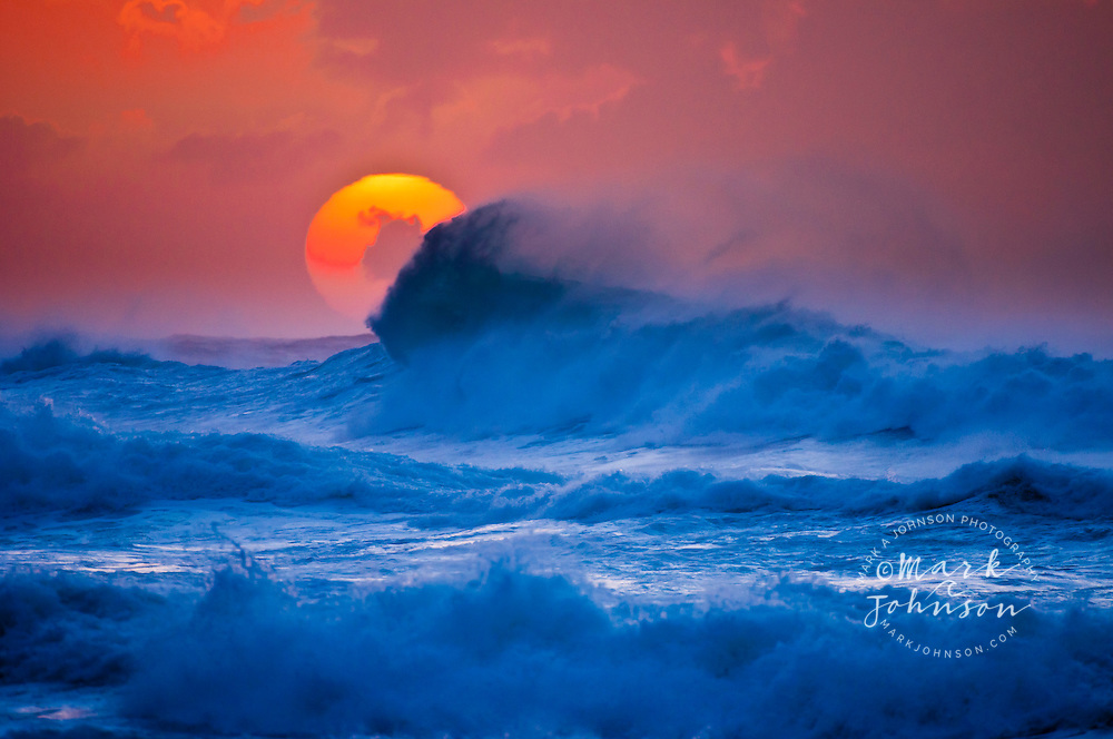 The setting sun and large winter waves breaking off Ke'e Beach, Kauai, Hawaii