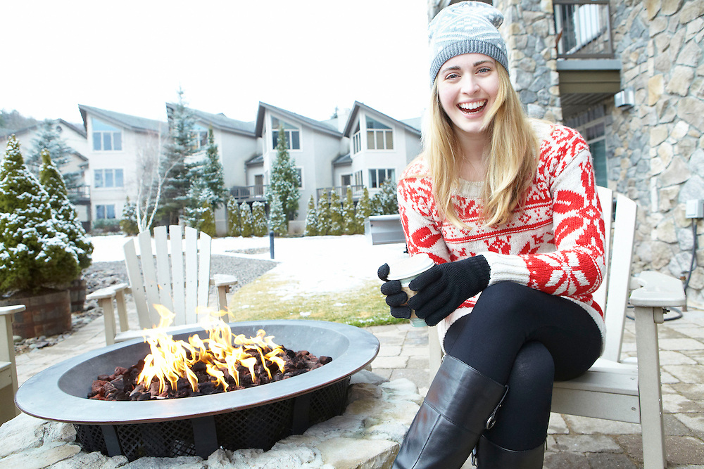 Lifestyle image of smiling girl with coffee sitting outside in front of fire during winter