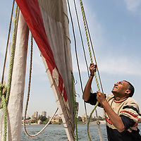 Egypt, Cairo, Captain pulls lines to raise sail of wooden dhow boat sailing on Nile River